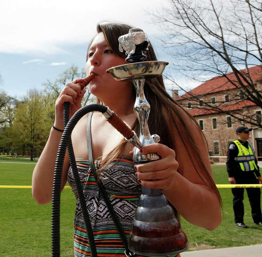 A student uses a water pipe to smoke marijuana outside the police barrier on the Norlin Quad at the University of Colorado in Boulder, Colo., on Friday, April 20, 2012. Police blocked off the quad to prevent a 420 marijuana smoke out. (AP Photo/Ed Andrieski) Photo: Ed Andrieski