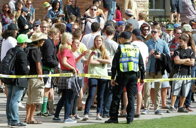 A sheriff's deputy talks to students behind police barrier on the Norlin Quad at the University of Colorado in Boulder, Colo., on Friday, April 20, 2012, at 4:20pm. Police blocked off the quad to prevent a 420 marijuana smoke out. (AP Photo/Ed Andrieski) Photo: Ed Andrieski