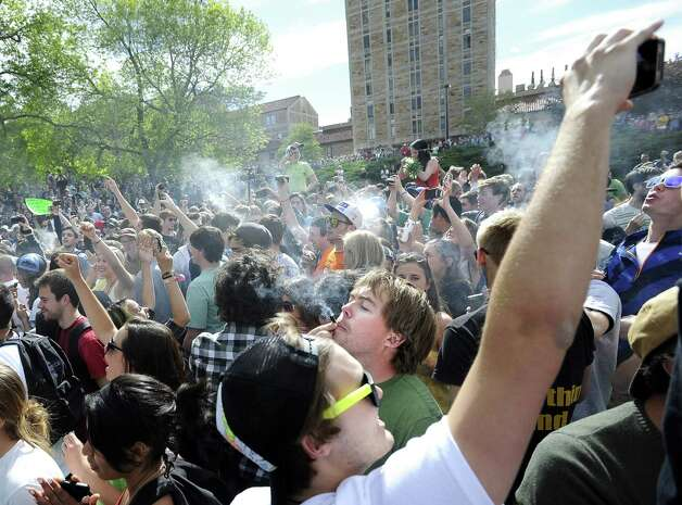 A crowd of marijuana supporters light up at 4:20 p.m. outside the Duane Physics building during the 4/20 rally on the University of Colorado campus in Boulder, Colo., on Friday, April 20, 2012. Many students at the University of Colorado and other campuses across the country have long observed 4/20. The counterculture observation is shared by marijuana users from San Francisco's Golden Gate Park to New York's Greenwich Village. (AP Photo/The Daily Camera, Jeremy Papasso) Photo: Jeremy Papasso