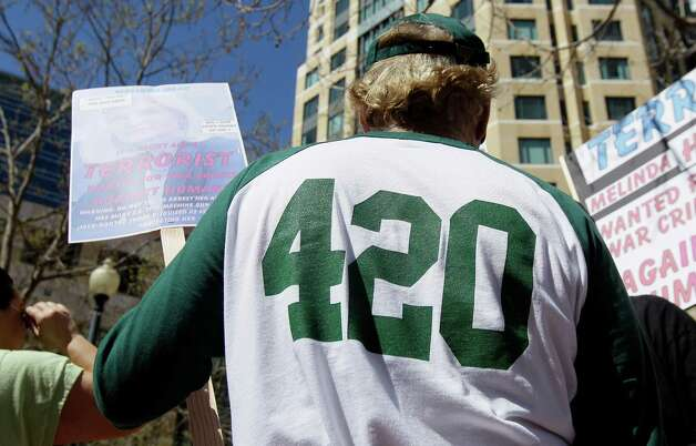 Medical marijuana supporter J.W. Marshall wears a 420 shirt from Oaksterdam University during a rally outside of the Ronald V. Dellums Federal Buidling in Oakland, Calif., Friday, April 20, 2012. (AP Photo/Jeff Chiu) Photo: Jeff Chiu