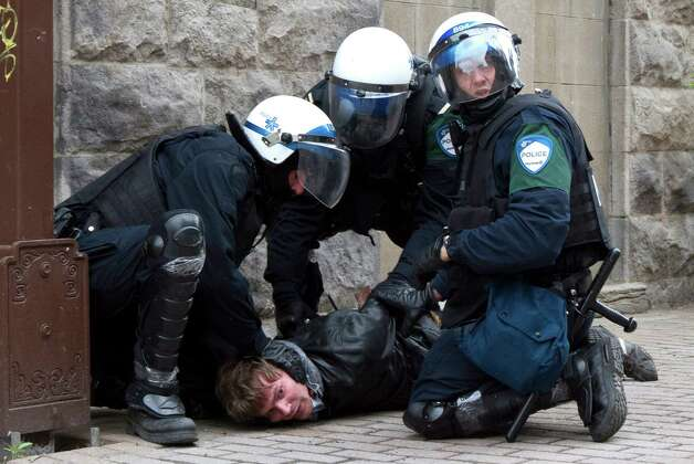 Police arrest a demonstrator outside the Montreal Convention Centre during a student demonstration against hikes to university and college tuition fees Friday, April 20, 2012 in Montreal. (AP Photo/The Canadian Press, Marie-Esperance Cerda) Photo: Marie-Esperance Cerda