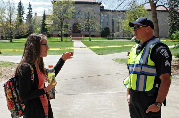 Boulder County Sheriff Sgt. Jeff Goetz, gives directions to sophomore Baylee Thenell at the Norlin Quad at the University of Colorado in Boulder, Colo., on Friday, April 20, 2012. The university closed the area and the campus from visitors to prohibit an annual 420 marijuana smoke out. (AP Photo/Ed Andrieski) Photo: Ed Andrieski