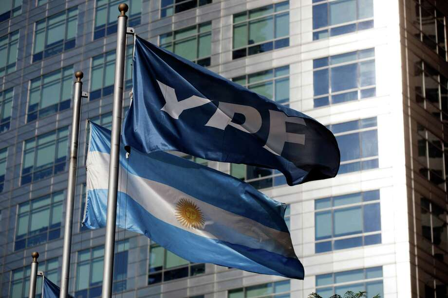 An Argentine flag and a flag of the YPF oil company in front of the YPF headquarters in Buenos Aires, symbolize Argentina's actions. Photo: Natacha Pisarenko / AP