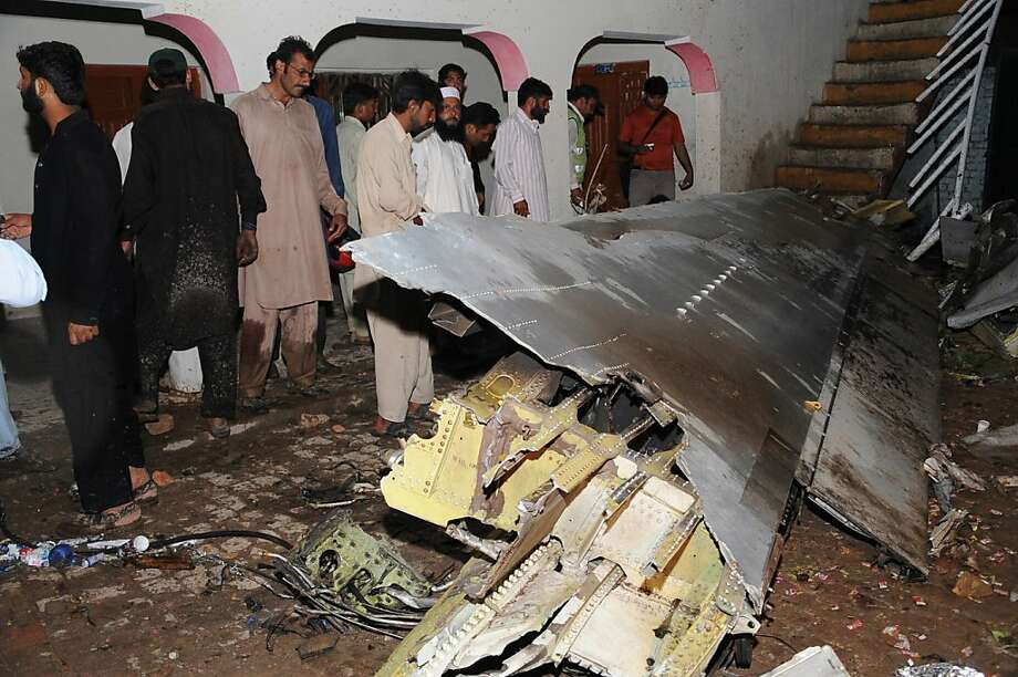 Pakistani villagers look at the debris from a plane following the crash of a Bhoja Air Boeing 737 on the outskirts of Islamabad on April 20, 2012.  Up to 130 people are feared dead after a Boeing 737 crashed while trying to land in bad weather near the Pakistani capital Islamabad today, officials said. Photo: Farooq Naeem, AFP/Getty Images