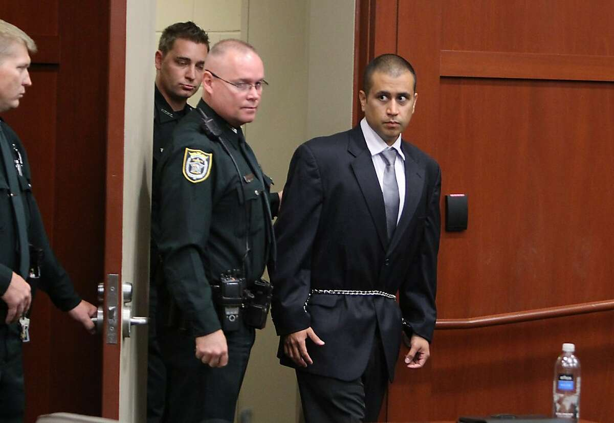George Zimmerman (R) is lead into a Seminole County courtroom for his bond hearing on April 20, 2012 in Sanford, Florida. Trayvon Martin was shot by George Zimmerman, a member of a neighborhood watch in Sanford, Florida, who has been charged with second degree murder in the shooting. Bail was set at $150,000 and Zimmerman and could be released from jail as he awaits trial as early as April 21. (Photo by Gary Green/The Orlando Sentinel-Pool/Getty Images)