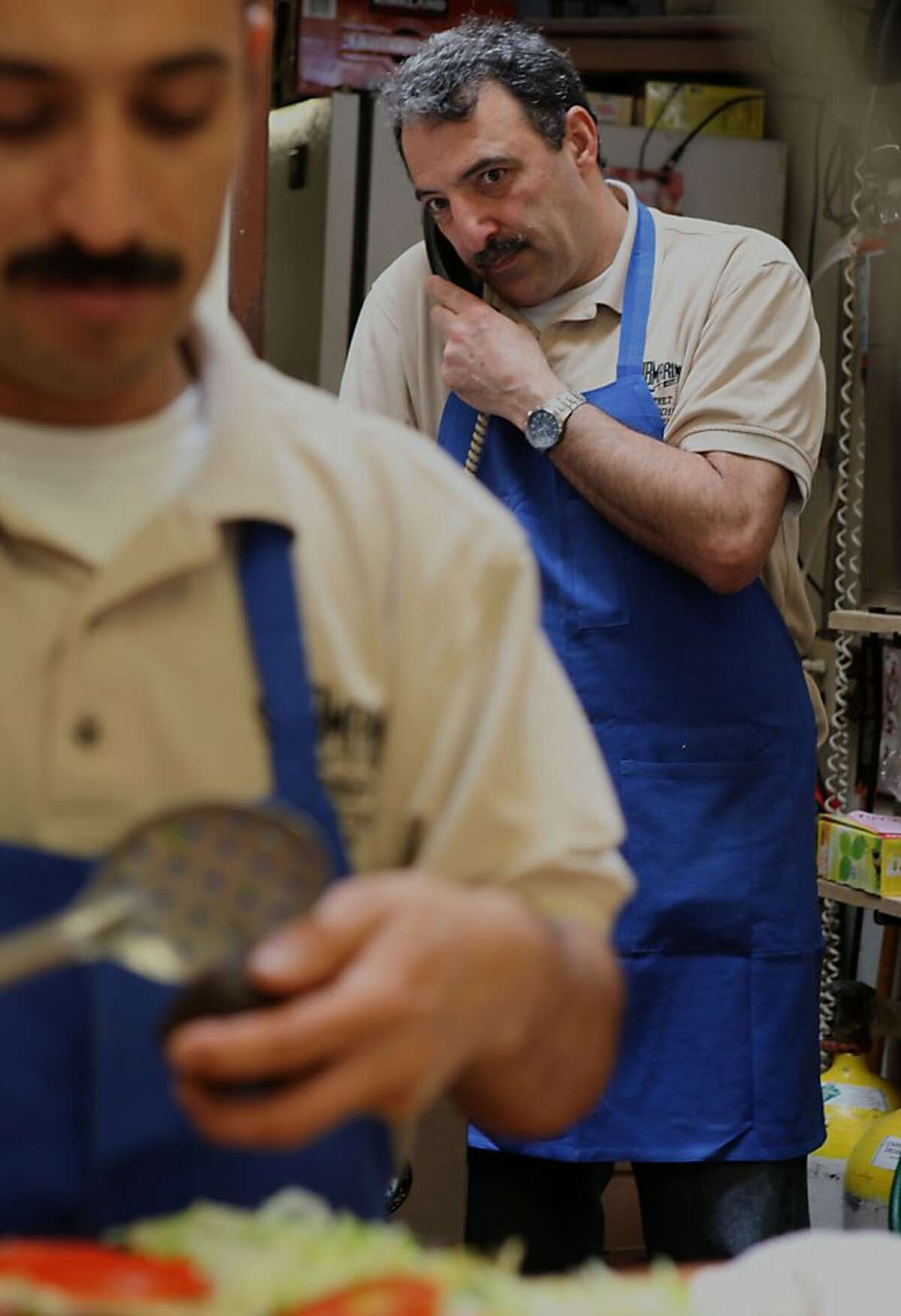 Adrian Hernandes (left) making a sandwich as longtime manager Rafik Zadoorian (right) takes a phone call at the Submarine Center in San Francisco, Calif., on Wednesday, April 11, 2012.