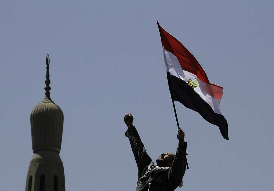 An Egyptian protester chants slogans and waves a national flag in front of a minaret at Tahrir Square, the focal point of Egyptian uprising, in Cairo, Egypt, Friday, April 20, 2012. Tens of thousands of protesters packed Cairo's downtown Tahrir Square on Friday in the biggest demonstration in months against the ruling military, aimed at stepping up pressure on the generals to hand over power to civilians and bar ex-regime members from running in upcoming presidential elections. Photo: Amr Nabil, Associated Press