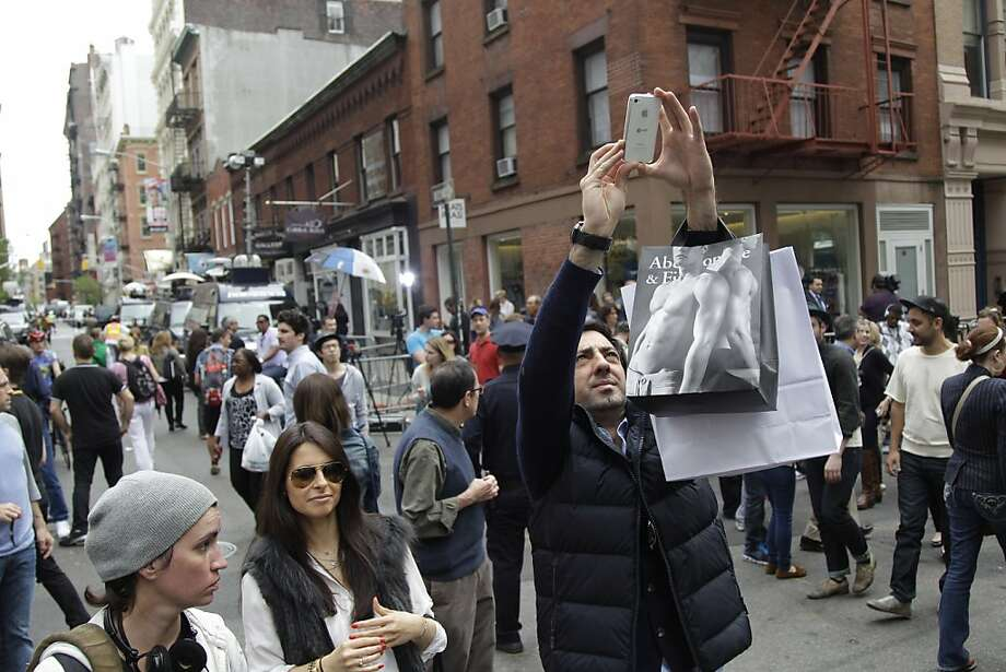 Tourists take photos of the scene outside the building on the corner of Wooster Street and Prince Street in the Manhattan borough of New York on Friday, April 20, 2012 during a renewed investigation into the 1979 disappearance of 6-year-old EtanPatz. Patz vanished after leaving his family's home for a short walk to his school bus stop. NYPD spokesperson Paul Browne says the building being searched for his remains is about a block from where the family lived.  (AP Photo/Mary Altaffer) Photo: Mary Altaffer, Associated Press