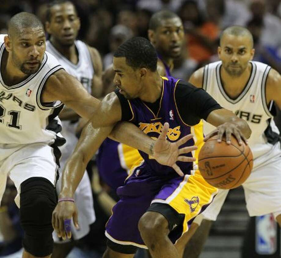 Spurs' Tim Duncan (21) reaches to attempt a steal against Los Angeles Lakers' Ramon Sessions (07) in the first half at the AT&T Center on Friday, Apr. 20, 2012. Kin Man Hui/Express-News. (San Antonio Express-News)