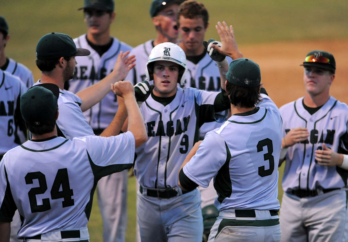 Reagan's Bryan Warhurst (9) is congratulated by his teammates after scoring a run during a 26-5A varsity baseball game between the Johnson Jaguars and the Reagan Rattlers on April 20, 2012 a the NEISD Blossom Baseball Field in San Antonio Texas. John Albright / Special to the Express-News.