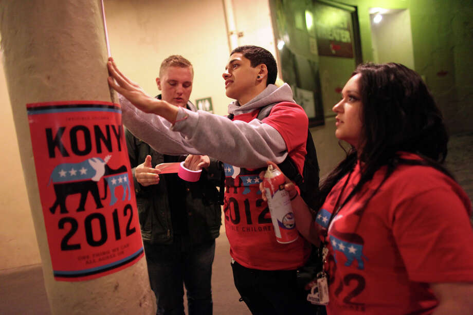 "Andy Vargas, 18, center, and Shaelyn Hood, 17, both of Stanwood, stick a poster to a pole near Pike Place Market during ""Cover the Night,"" part of the Kony 2012 campaign. The controversial campaign by the group Invisible Children is working to bring attention to Joseph Kony, leader of the Lord's Resistance Army in Africa. Photographed on Friday, April 20, 2012. Photo: JOSHUA TRUJILLO / SEATTLEPI.COM"
