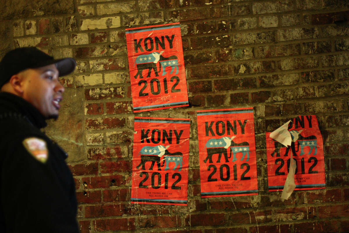 A security officer warns participants not to affix posters on Pike Place Market property during