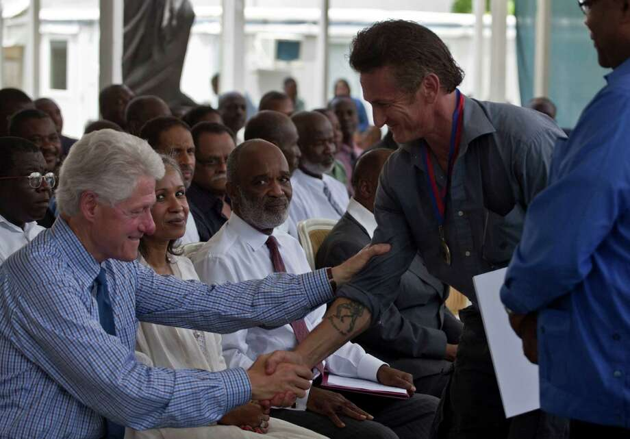 FILE - In this Monday, July 12, 2010 file photo, former U.S. President and U.N. special envoy for Haiti, Bill Clinton, left, shakes hands with U.S. actor Sean Penn after Penn received a medal for the assistance provided to Haiti during a memorial ceremony at the National Palace on the six-month anniversary of the Jan. 12, 2010 earthquake in Port-au-Prince, Haiti. Seated at center is President Rene Preval. The actor who stormed onto the scene of one of the worst natural disasters in history two years ago has certainly not lost interest. Defying skeptics, he has put down roots in Haiti, a country he hadn't even visited before the January 2010 earthquake, and has become a major figure in the effort to rebuild. (AP Photo/Ramon Espinosa) Photo: Ramon Espinosa