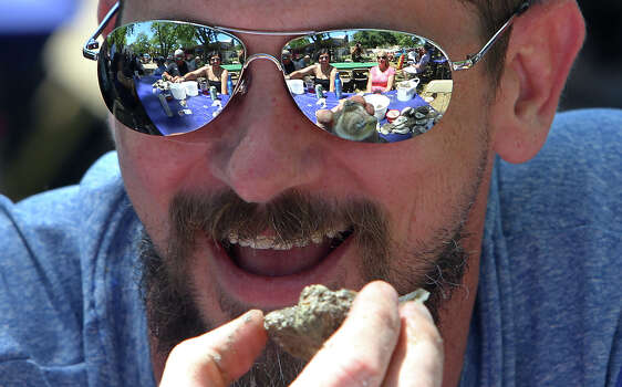 Ryan Wannemacher gets ready to devour a baked oyster as the scene of friends and shucked oysters reflect off his sunglasses at the 2012 Fiesta Oyster Bake at St. Mary's University on Saturday, Apr. 21, 2012. Proceeds from the event go toward scholarships and university programs. Photo: Kin Man Hui, Kin Man Hui/Express-News / ©2012 San Antonio Express-News