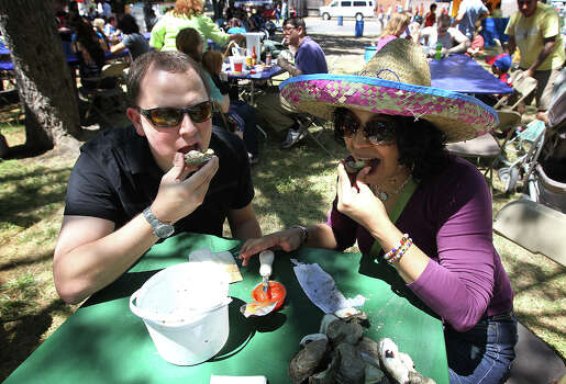 First-timer Harold Creger (left) joins Lisa Marie Gomez in eating a baked oyster at the 2012 Fiesta Oyster Bake at St. Mary's University on Saturday, Apr. 21, 2012. Proceeds from the event go toward scholarships and university programs. Photo: Kin Man Hui, Kin Man Hui/Express-News / ©2012 San Antonio Express-News