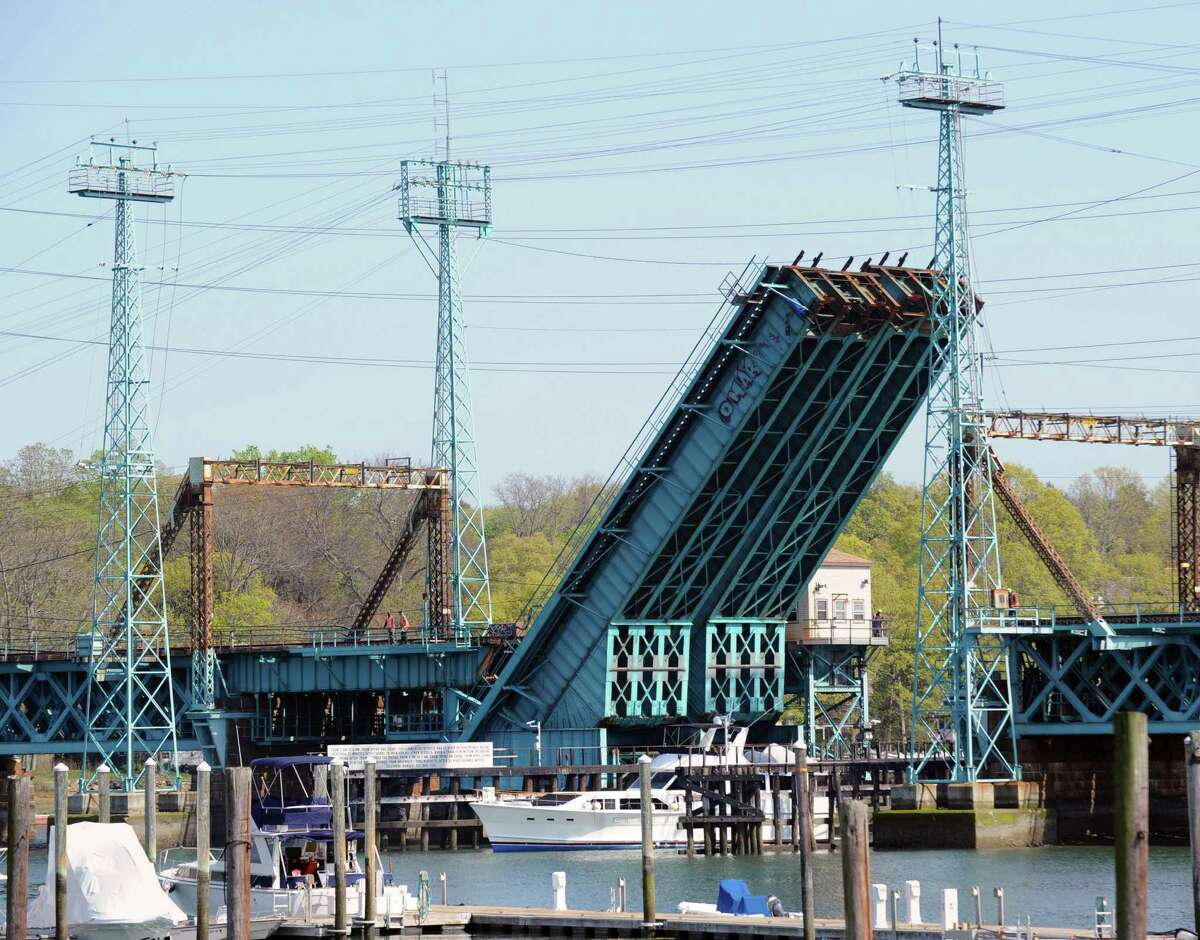 A boat passes under the raised Cos Cob railroad bridge, Thursday afternoon, April 19, 2012. The Cos Cob moveable railroad bridge is more than a century old.