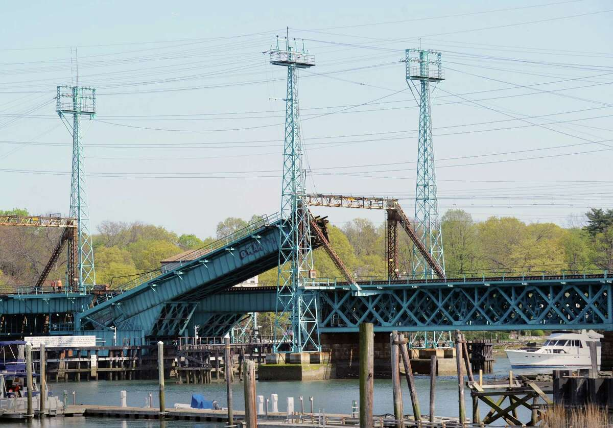 A boat waits for the Cos Cob railroad bridge to be raised before passing through, Thursday afternoon, April 19, 2012. The Cos Cob moveable railroad bridge is more than a century old.