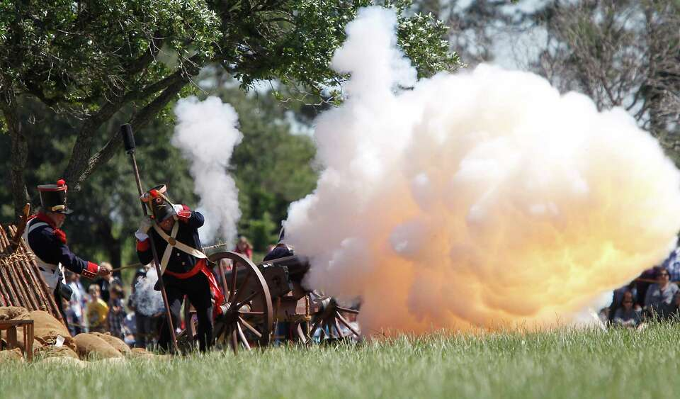 Reenactors dressed in Mexican army uniforms fire a cannon during the San Jacinto battleground reenac