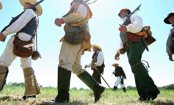 Reenactors dressed as Texian soldiers walk along the battlefield during the battle reenactment commemorating the 176th anniversary of the battle of San Jacinto at the San Jacinto Battleground, Saturday, April 21, 2012, in Houston. Photo: Karen Warren, Houston Chronicle / © 2012  Houston Chronicle