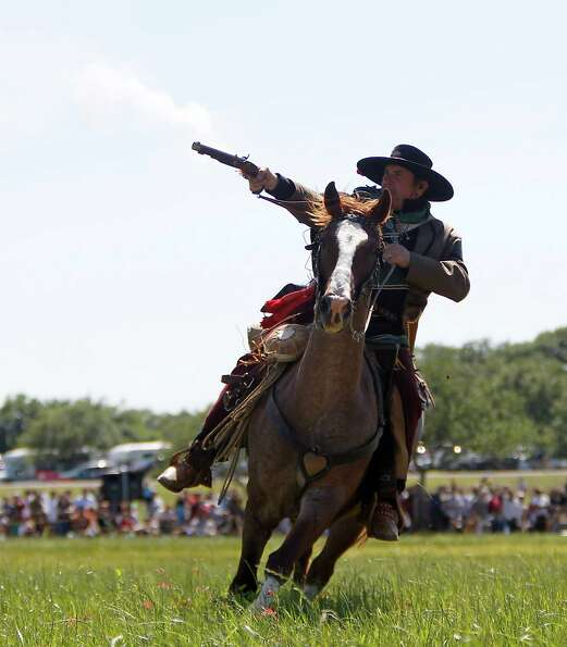 A Texian Army reenactor fires a gun while on horseback during the battle reenactment commemorating t