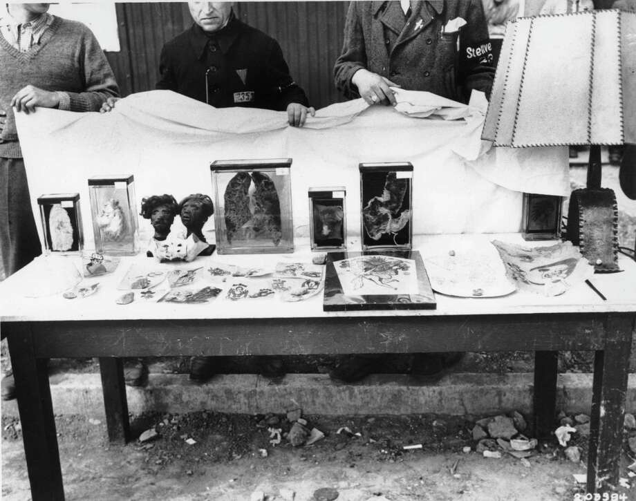An exhibition of barbarism was seized by Gen. Patton's 3rd  U.S. Army during World War II at Germany's Buchenwald concentration camp, seen April 16, 1945. These 'souvenirs' were fashioned by the Nazis from heads of dead prisoners, shrunken to miniature size. Left are parts of human organs, stencilings and tattoo markings on skin. On the right is a lamp fabricated from human skin. German citizens from nearby Weimar were ordered to the camp to view the exhibit. (AP Photo/U.S. Army) Photo: Anonymous, ASSOCIATED PRESS / AP1945