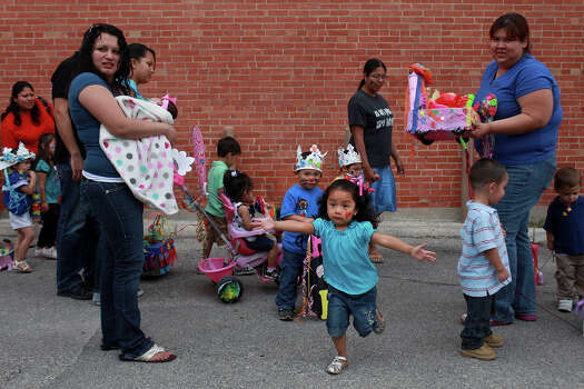 metro - Ximena Celestino, 2, center, runs towards her mother, Teresa Lagunas, not pictured, as teacher Amelia Espinoza, far right, watches and Megan Delgado, left, holds her daughter, Audrey Castro, 2 months, during their Fiesta parade, part of the bi-monthly socialization activity for AVANCE's home-based option of early Head Start at the organization's headquarters in San Antonio on Friday, April 20, 2012. Lisa Krantz/San Antonio Express-News Photo: Lisa Krantz, SAN ANTONIO EXPRESS-NEWS / SAN ANTONIO EXPRESS-NEWS