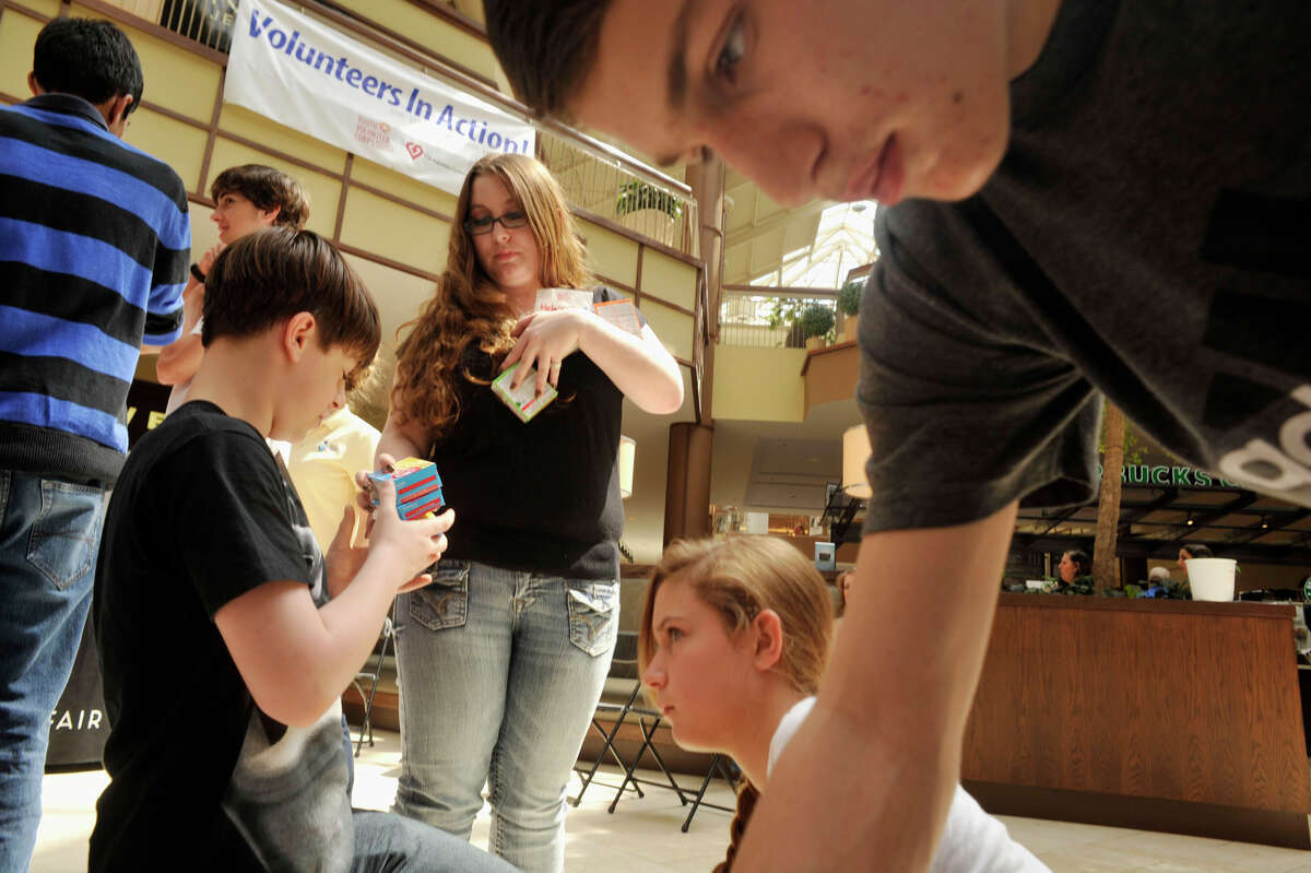From left, David DuBack, 13, and sister Rebecca DuBack, 17, both of Danbury, Tessa Doyle, 13, of Danbury, and Anthony Sasso, 14, of Danbury, organize food into more than 15 groups on the floor of the mall during the Youth Volunteer Corps of Western Connecticut's building of a healthy wall of food at the Danbury Fair mall on Global Youth Service Day on Saturday, April 21, 2012.