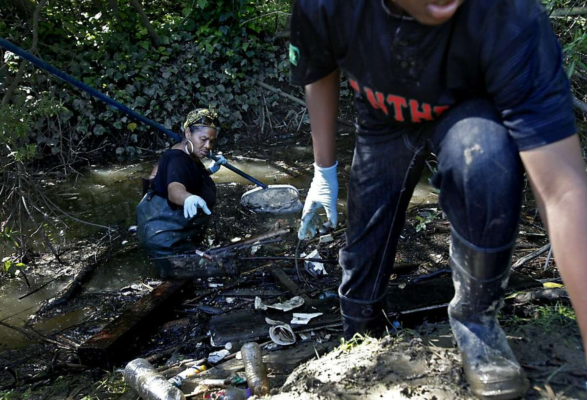 Roxanne Alexander, left, and Alonzo Harden Jr., 13, right, pick trash out of the Wildcat Creek as part of an Earth Day cleanup in Richmond, Calif., Saturday, April 21, 2012.
