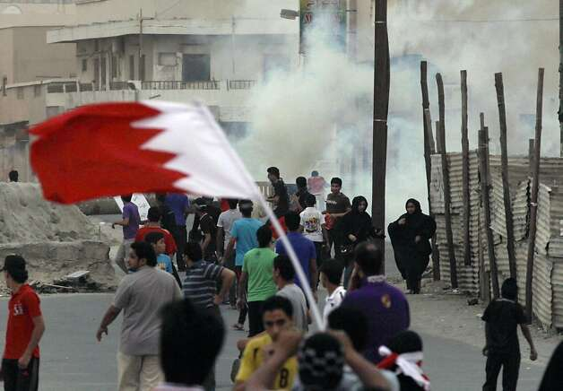 Bahraini anti-government protesters, one carrying a national flag, react to tear gas fired by riot police Saturday, April 21, 2012, in Diraz, Bahrain, west of the capital of Manama. Bahraini opposition groups claimed Saturday that a man was killed during clashes with security forces, threatening to sharply escalate the Gulf nation's unrest as officials struggle under the world's spotlight as hosts of the Formula One Grand Prix. Authorities opened an investigation in a bid to diffuse tensions. Photo: Hasan Jamali, Associated Press