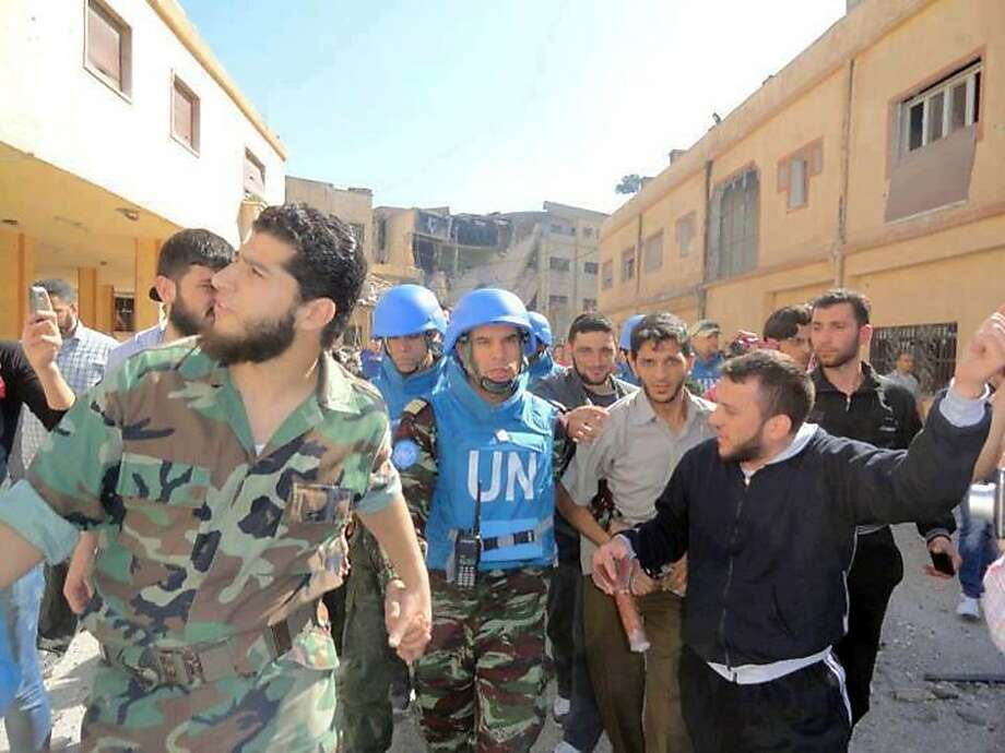 A handout picture released by Shaam News Network on April 21, 2012, shows Abdul Razzaq Tlas (L) leader of the opposition Katibat al-Faruq, holding the hand of Moroccan UN observer, Colonel Ahmed Himmiche  during the monitor's visit to the restive city of Homs on April 21, 2012. Photo: -, AFP/Getty Images