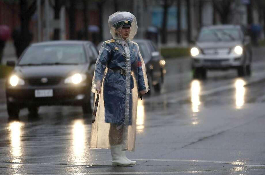 A North Korea traffic coordinator wears a plastic raincoat while on duty in Pyongyang, North Korea, Saturday, April 21, 2012. (AP Photo/Ng Han Guan) Photo: Ng Han Guan, Associated Press