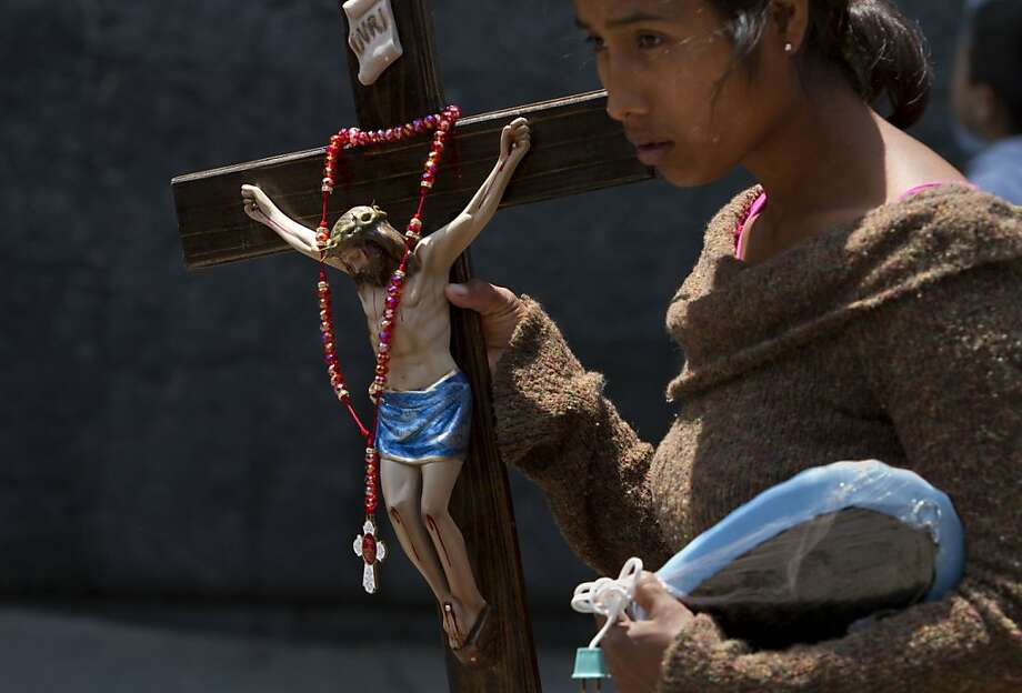 A woman carries a statue of Jesus as worshipers attend the beatification ceremony for the late sister Maria Ines Teresa Arias at the Basilica of Our Lady of Guadalupe in Mexico City, Saturday, April 21, 2012. The Mexican nun, who founded the Congregation of Poor Clare Missionary Sisters, was beatified at the Basilica on Saturday. Beatification is a first step toward sainthood. (AP Photo/Dieu Nalio Chery) Photo: Dieu Nalio Chery, Associated Press
