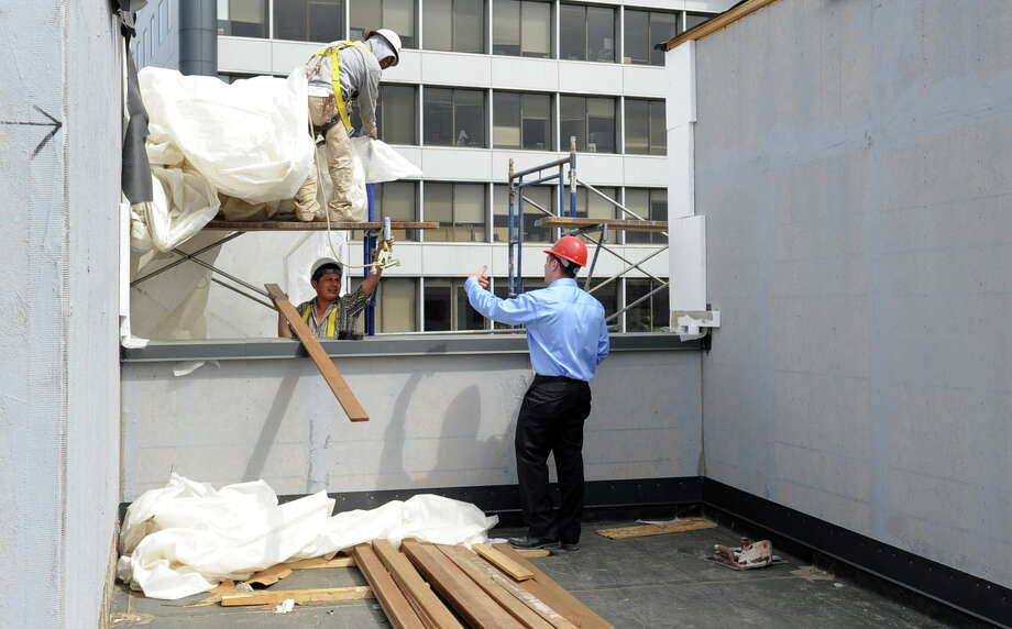 Jonathan Cohen, Director of Operations and Safety for RMS Companies, calls Jose Ortega off of scaffolding to give him a few tips about his safety harness as he works on Parallel 41, a luxury apartment building on Washington Blvd. in Stamford, on Wednesday, April 18, 2012. The workers all wear harnesses to minimize the risk of falls on the site. Photo: Lindsay Niegelberg / Stamford Advocate