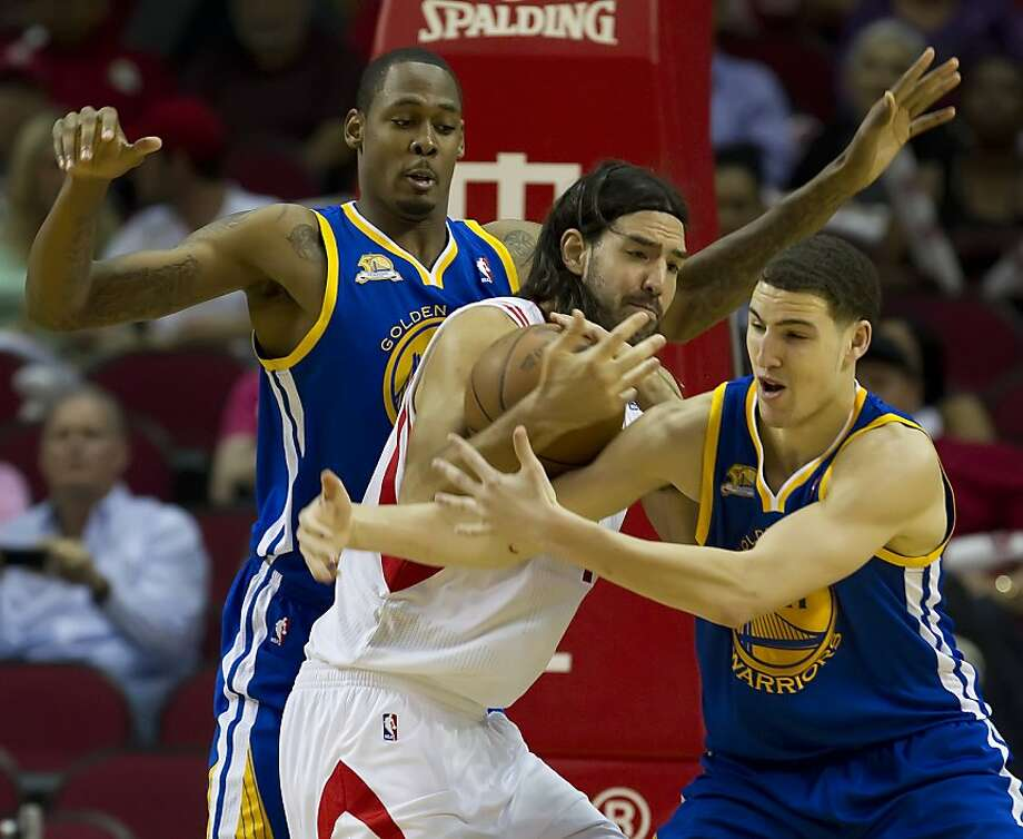 Luis Scola (4) of the Houston Rockets fights through the defense of Klay Thompson (11), right, and Mickell Gladness (32) of the Golden State Warriors in the second half of the Rockets' 99-96 victory on Saturday, April 21, 2012, in Houston, Texas. Photo: George Bridges, McClatchy-Tribune News Service