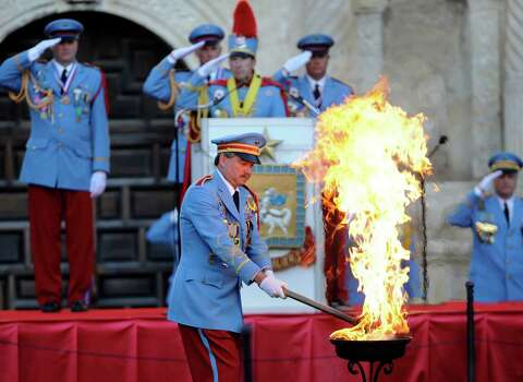 William Franklin Mitchell, last year's King Antonio, lights a flame as the new King Antonio, Tom Green, at podium, and other members of the Texas Cavalliers, salute during Green's investiture in Alamo Plaza on Saturday, April 21, 2012. Billy Calzada / Express-News Photo: BILLY CALZADA, SAN ANTONIO EXPRESS-NEWS / San Antonio Express-News