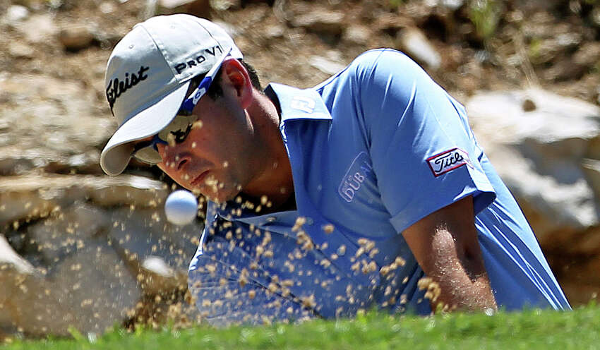 Ben Curtis gets his second try to escape the sand trap at the first green during the third round of the 2012 Valero Texas Open on Saturday, April 21, 2012.