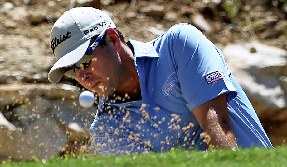 Ben Curtis blasts from the greenside bunker at No. 1 on his second try Saturday at TPC San Antonio. Curtis, the third-round leader after shooting 73, carded a double-bogey six on the hole. Photo: TOM REEL, San Antonio Express-News / San Antonio Express-News