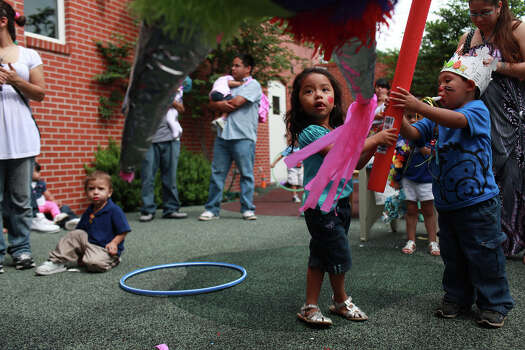 metro - Ximena Celestino, 2, right, and Nazareth Maldonado, 2, far right, hit a pinata before their Fiesta parade, for the bi-monthly socialization activity for AVANCE's home-based option of early Head Start at the organization's headquarters in San Antonio on Friday, April 20, 2012. Lisa Krantz/San Antonio Express-News Photo: Lisa Krantz, SAN ANTONIO EXPRESS-NEWS / SAN ANTONIO EXPRESS-NEWS