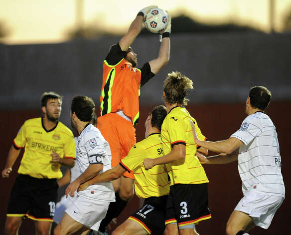 Fort Lauderdale goalkeeper Matt Glaeser leaps to grab a ball in traffic during a match between the Scorpions and the Fort Lauderdale Strikers on Saturday, April 21, 2012 at Heroes Stadium. Photo: John Albright, For The Express-News
