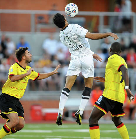 The Scorpions' Pablo Campos (9) leaps to control a ball between two Fort Lauderdale players during their match on Saturday, April 21, 2012 at Heroes Stadium. Photo: John Albright, For The Express-News
