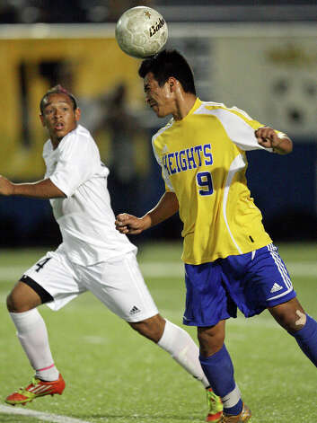 Alamo Heights' Christian Garcia heads a ball as Wichita Falls Rider's Juan Orozco looks on during first half action of the Class 4A state final game Saturday, April 21, 2012 at Birkelbach Field in Georgetown. Photo: EDWARD A. ORNELAS, San Antonio Express-News / © SAN ANTONIO EXPRESS-NEWS (NFS)