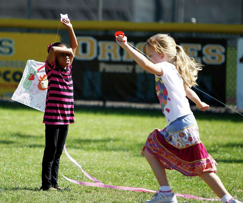 Cameron Jackson, 8, left, tries to fly a kite as a classmate runs by her during Kite Day at T.H. Rogers in Houston ISD, Thursday, April 19, 2012, in Houston, which has been named the best elementary and middle school in the greater Houston area, according to the 2011 rankings from Children at Risk. The school is unique in that it serves gifted students as well as deaf students and multiply impaired students. The rankings are based mostly on the test scores of the gifted students and some of the deaf students. Photo: Karen Warren, Houston Chronicle / © 2012  Houston Chronicle