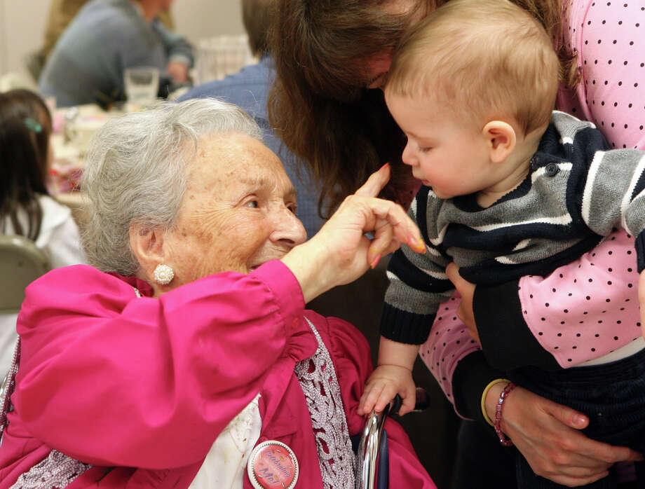 Theresa Vas Nunes, 100, touches the tip of Joshua Glassman's nose, 8 mos, at the Jewish Home of Fairfield County's annual 100th Birthday party for centenarians on Sunday, April 22, 2012 in Fairfield, Conn. Photo: B.K. Angeletti / Connecticut Post