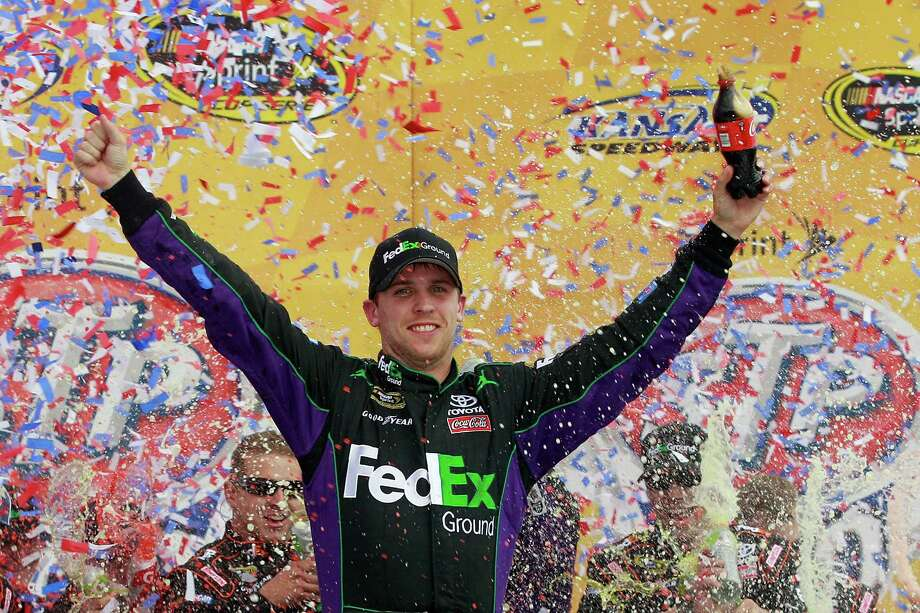 Denny Hamlin, driver of the #11 FedEx Ground Toyota, celebrates in victory lane after he won the NASCAR Sprint Cup Series STP 400 at Kansas Speedway on April 22, 2012 in Kansas City, Kansas. Photo: Chris Graythen, Getty Images For NASCAR / 2012 Getty Images