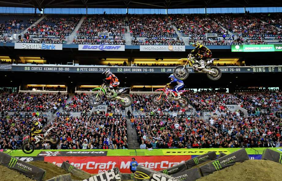Riders fly off a jump during a Supercross Lites qualifying heat of the Monster Energy AMA Supercross event at CenturyLink Field on   Saturday,  April 21, 2012. The field was transformed into a giant dirt  track for the event, where riders from all over the U.S.  competed for  the title and cash prizes before a crowd of 52,731 fans. The No.  1-ranked Poulsbo native Ryan Villopoto was heavily favored to win the  title, but suffered a crash during the first lap of the main event,  putting him out of the competition. Texas native Andrew Short ended up  winning the main event,  despite injuries earlier in the season. Photo: LINDSEY WASSON / SEATTLEPI.COM