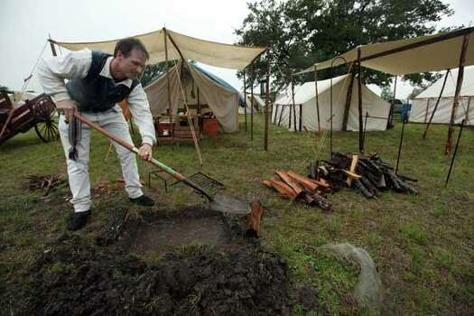 Michael Sproat dishes out water from his fire pit in front of their tent at the San Jacinto Monument on Friday, April 20, 2012, in La Porte. The reenactment of the Battle of San Jacinto will be Saturday, April 21 at 3 p.m. near the reflection pool at the San Jacinto Monument. Photo: Mayra Beltran, Houston Chronicle / © 2012 Houston Chronicle