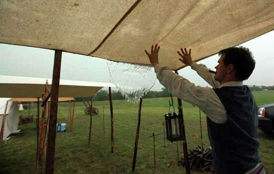 Michael Sproat pushes water off their tent at the Texas Army civilian camp at the San Jacinto Monument on Friday, April 20, 2012, in La Porte. The reenactment of the Battle of San Jacinto will be Saturday, April 21 at 3 p.m. near the reflection pool at the San Jacinto Monument. Photo: Mayra Beltran, Houston Chronicle / © 2012 Houston Chronicle