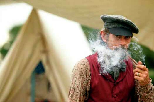 Jim Glover dressed in period clothing smokes a pipe outside his tent at the Texas Army civilian camp where history reenactors are setting up in preparation for the reenactment of the Battle of San Jacinto over the weekend on Friday, April 20, 2012, in La Porte.   The reenactment of the Battle of San Jacinto will be Saturday, April 21 at 3 p.m. near the reflection pool at the San Jacinto Monument. Photo: Mayra Beltran, Houston Chronicle / © 2012 Houston Chronicle