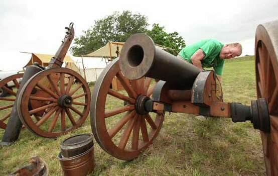 Robert Donahoo, of the San Jacinto Volunteers, flips over the cannon to protect barrel from the rain at the Texas Army civilian camp on Friday, April 20, 2012, in La Porte.   The reenactment of the Battle of San Jacinto will be Saturday, April 21 at 3 p.m. near the reflection pool at the San Jacinto Monument. Photo: Mayra Beltran, Houston Chronicle / 2012 Houston Chronicle