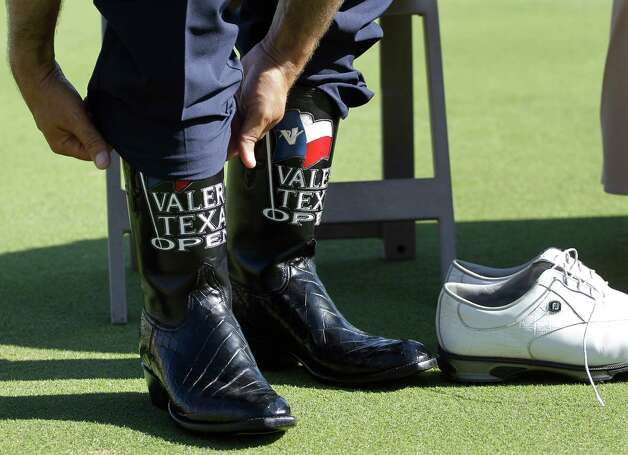 Ben Curtis trades his golf shoes for a pair of cowboys boots after winning the the Texas Open golf tournament on Sunday, April 22, 2012, in San Antonio. Curtis finished at 9 under par. Photo: AP